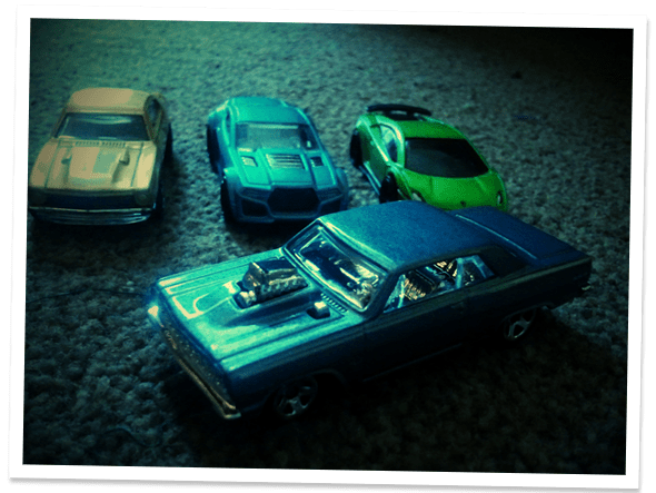Four small diecast metal cars.