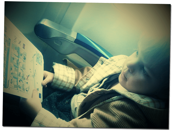 Lucien reading the safety instruction on our flight to the UK.