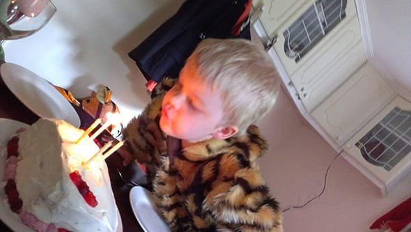 Lucien blowing out the four candles on his birthday cake.