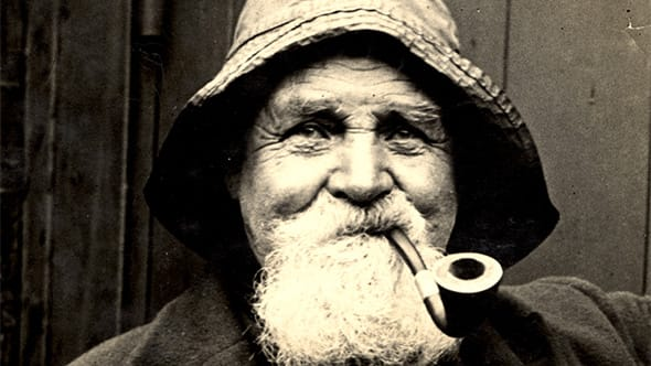 An old wrinkly man smoking a pipe.