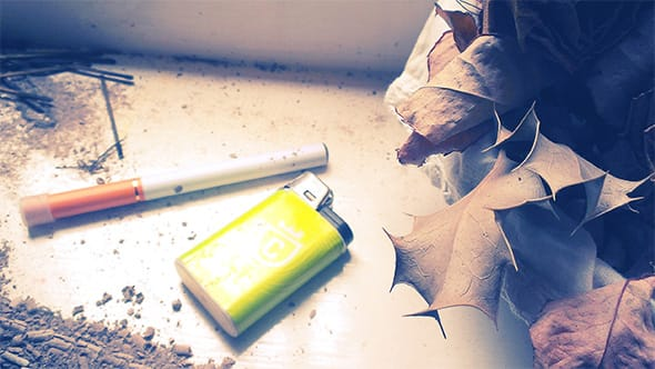 A cheap electronic cigarette lying next to a Colt lighter.