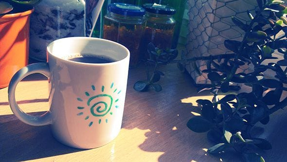 A coffee mug brightly lit by the morning sun.