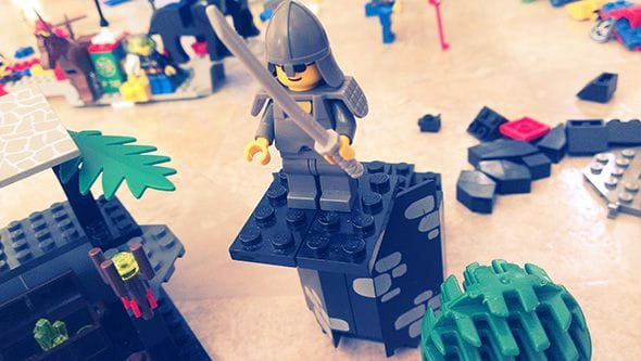 Cool looking Lego ninja standing atop a roof with a katana.