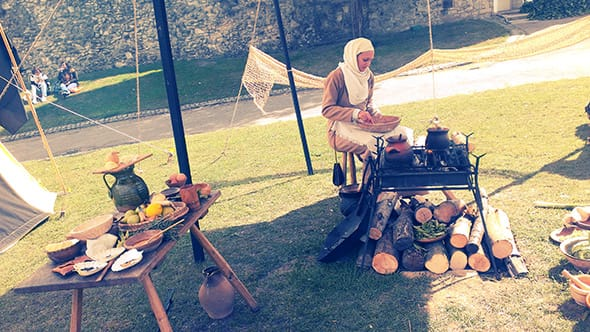 A woman dressed head to toe in medieval clothing making food at Rochester Castle.