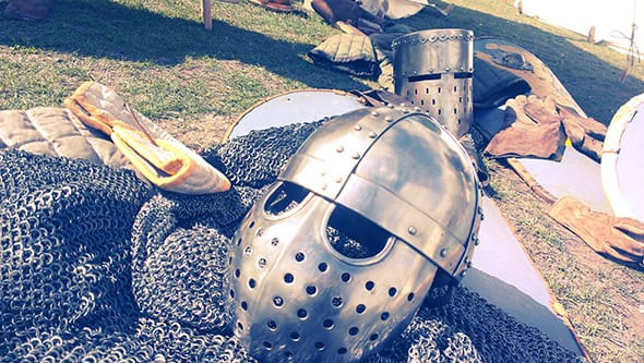 Real medieval helmets and chainmail armour on a table.