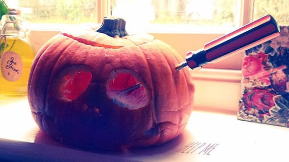 E decomposing pumpkin with a screwdriver driven through its fleshy head.