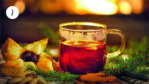 A glass of mulled wine in a beautiful Christmas setting, open fire in the background.
