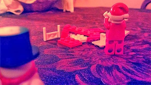 Lego santa is distraught to find his sledge destroyed by Lego Frosty the Snowman.