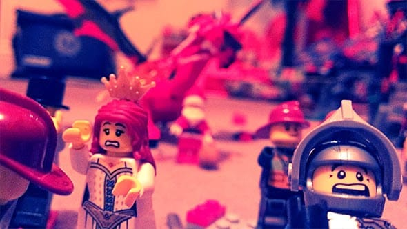 Lego minifigures running in terror as Lego santa and the Lego dragon attacks them, breathing fire everywhere.