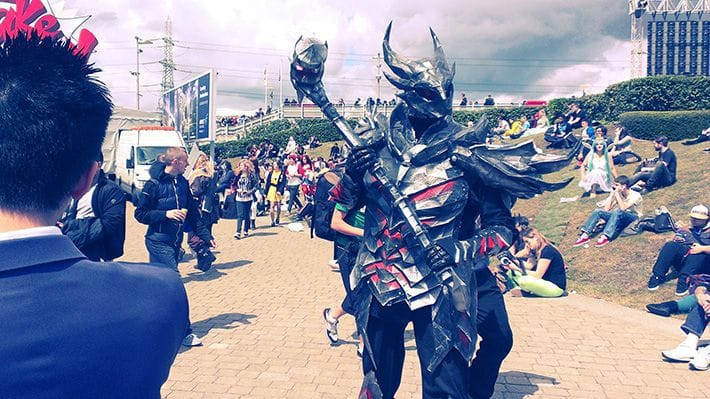 A cosplayer in a full set of Daedric Armor, from The Elder Scrolls series, with Daedric Warhammer.