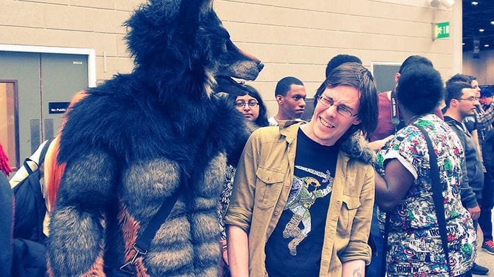 Carlos Eriksson pretending to be eating by a werewolf cosplayer.