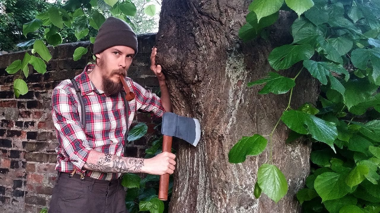 Carlos Eriksson dressed as a lumbersexual and posing next to a tree holding a faxe card board axe.