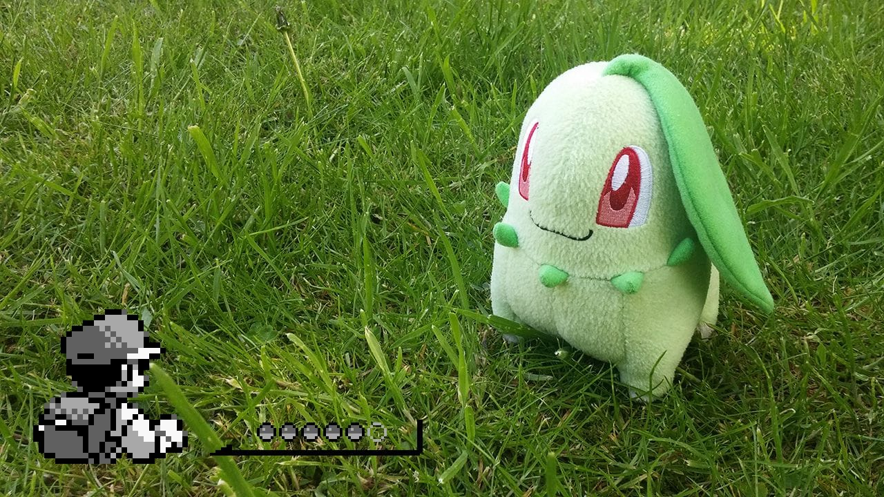 Chikorita plushie sitting in luscious green grass.