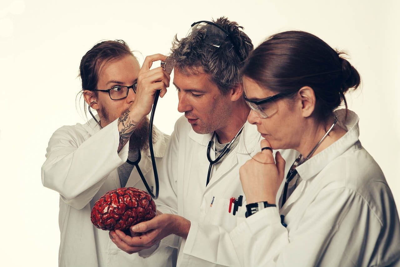 Carlos ignoring the brain in front of him and instead holding up a stethoscope to Kris's forehead.