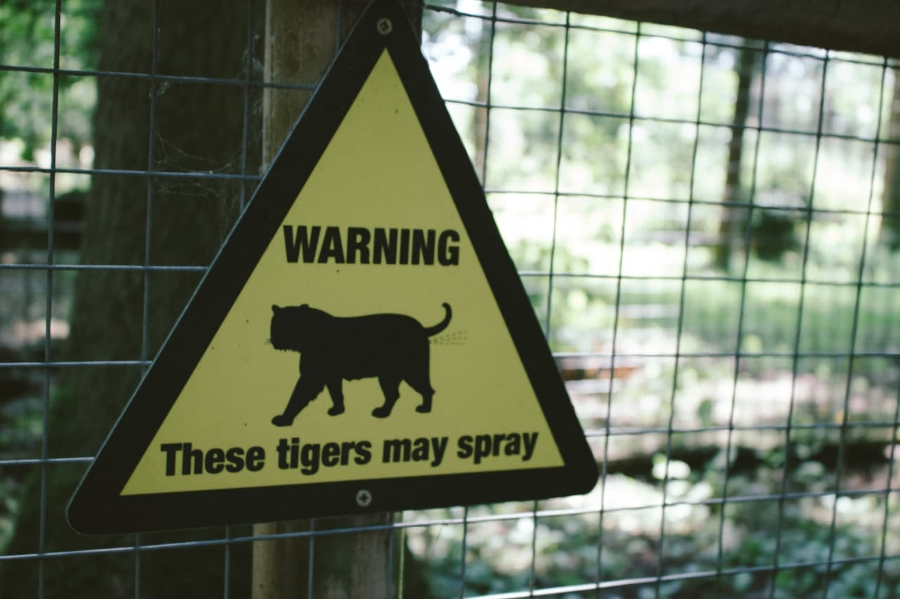 Sign warning for spraying tigers.