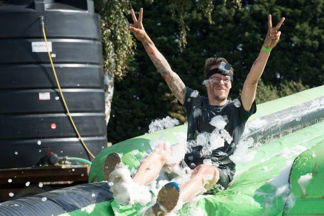 Carlos Eriksson sliding through foam and fairy liquid, giving the victory sign.