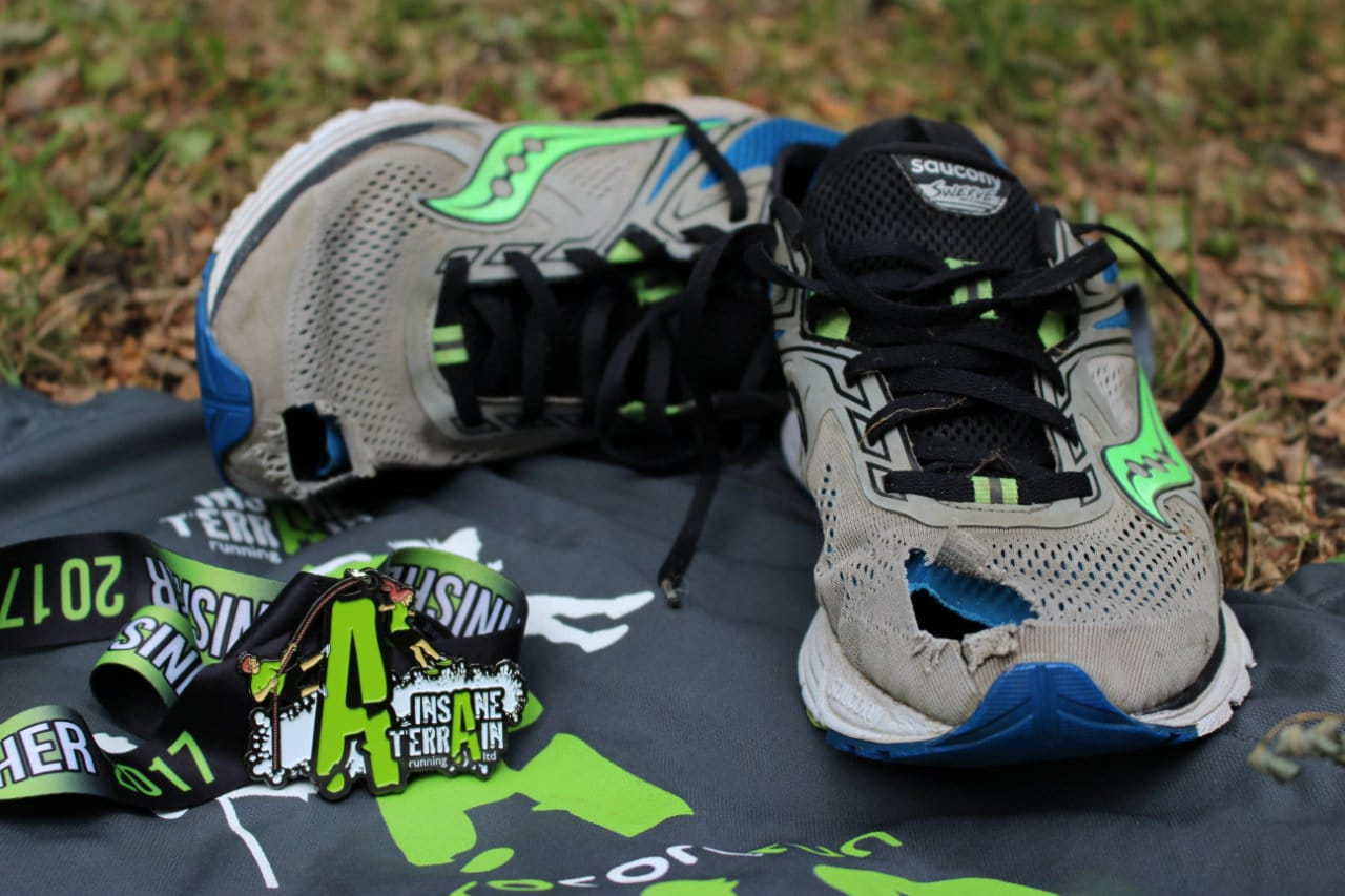 The Saucony Swerve with holes through the toes lying next to the Insane Terrain 2017 medal.
